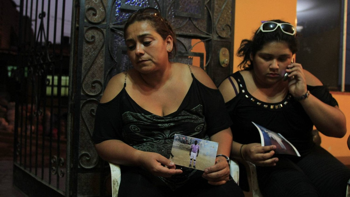 Patricia Aguilar, who lost her companion Enrique Arenaza, holds photos next to her daughter at her home in Comas.