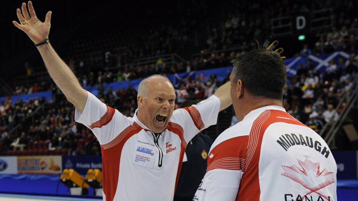 Canadian skip Glenn Howard, left, celebrates with third Wayne Middaugh after his rink beat Scotland 8-7 to win the gold medal at the world men's curling championship in Basel, Switzerland, Sunday.