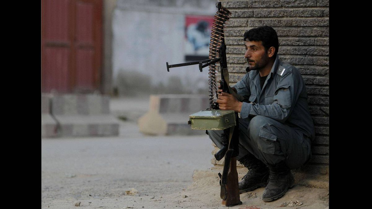 An Afghan policeman keeps guard at the site of a Taliban attack in Kabul April 15, 2012.