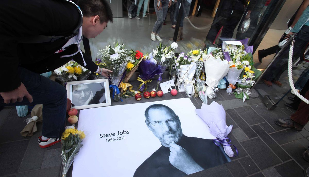 A Chinese man places a bouquet of white carnations beside a photo of Steve Jobs outside an Apple store in Beijing on October 6, 2011.