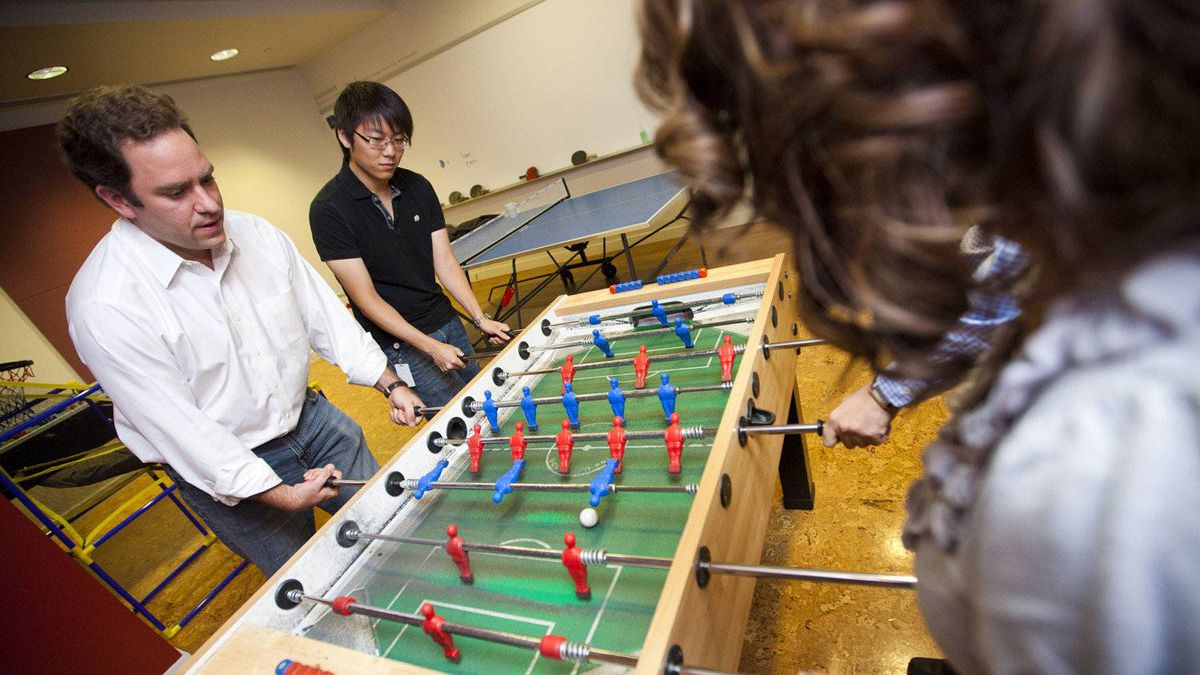 Capital One Canada president Rob Livingston, left, gets in a game of foosball with employees at their Toronto offices Wednesday.