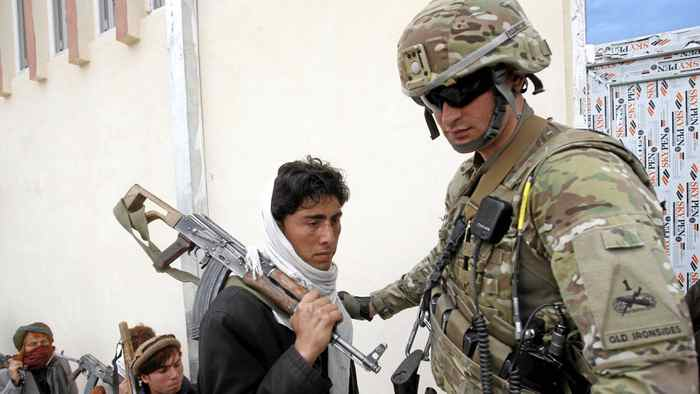 A U.S. soldier guides a Taliban militant, part of a group of a hundred Afghan Talibans, as he hands over his weapons as part of the Afghan government's reconciliation and reintegration program in Laghman province March 12, 2012.
