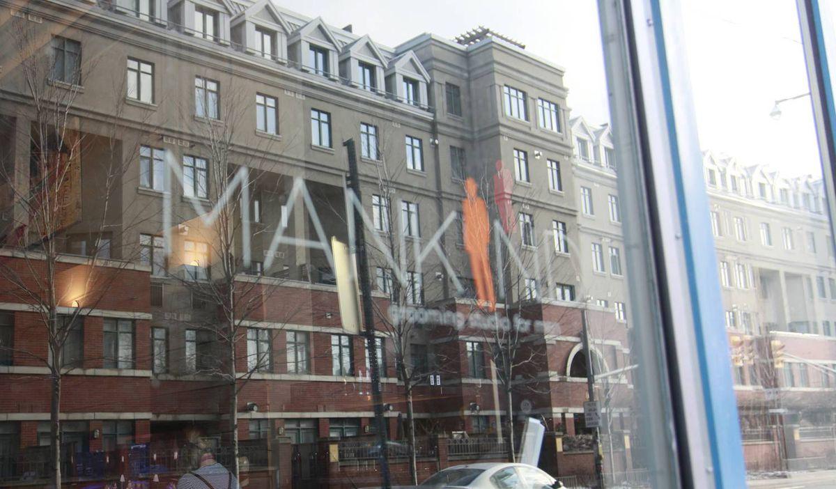 Mankind Grooming Studio for men logo seen in window's reflection