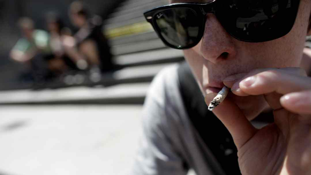 VANCOUVER, BRITISH COLUMBIA: July 8th, 2010 - An unidentified young man smokes a joint on the steps of the Vancouver Art Gallery on July 8th, 2010. Gallery employees are worried that marijuana smoke is getting into the museum via air vents.