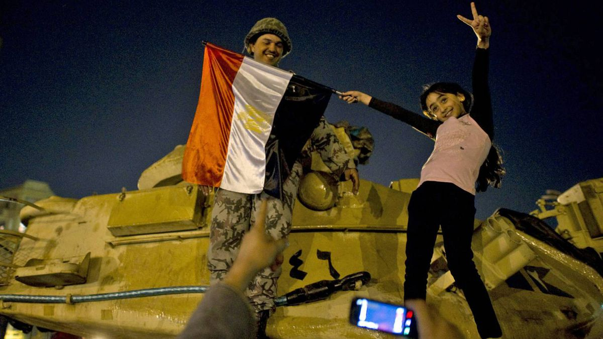 A girl poses with a soldier on top of a tank at Tahrir Square in Cairo early on Feb. 12, 2011.