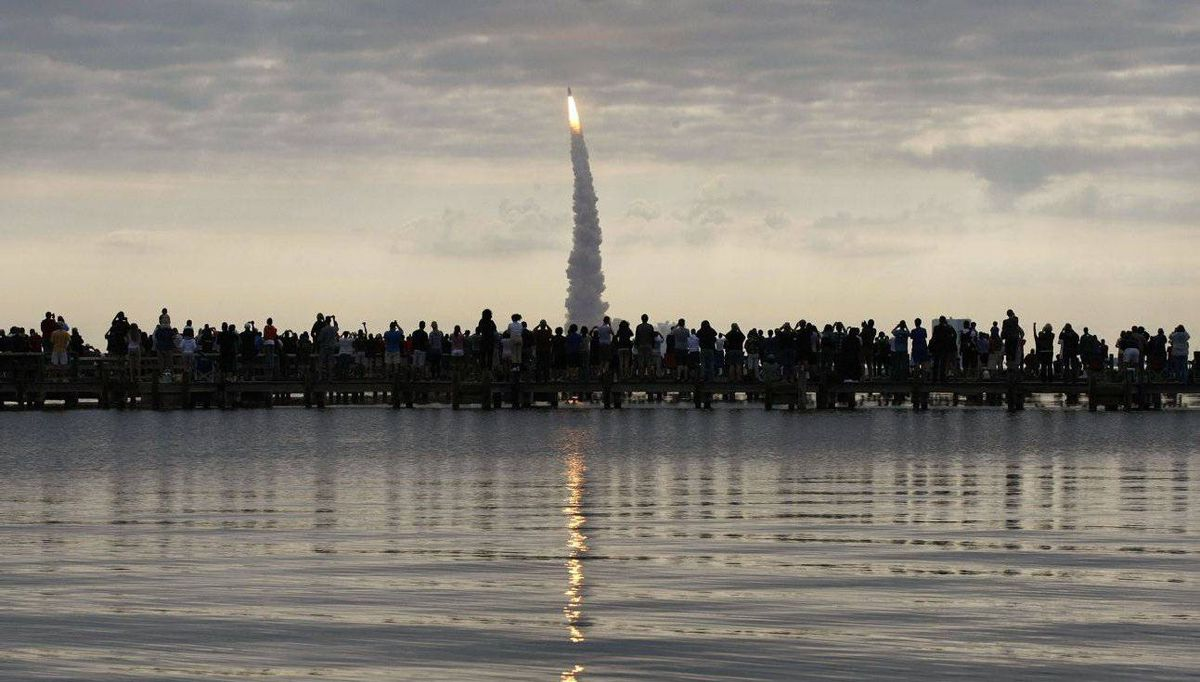 People watch as the space shuttle Endeavour lifts off from the Kennedy Space Center in Cape Canaveral, Florida. Endeavour carries a crew of six astronauts on a mission to the International Space Station.