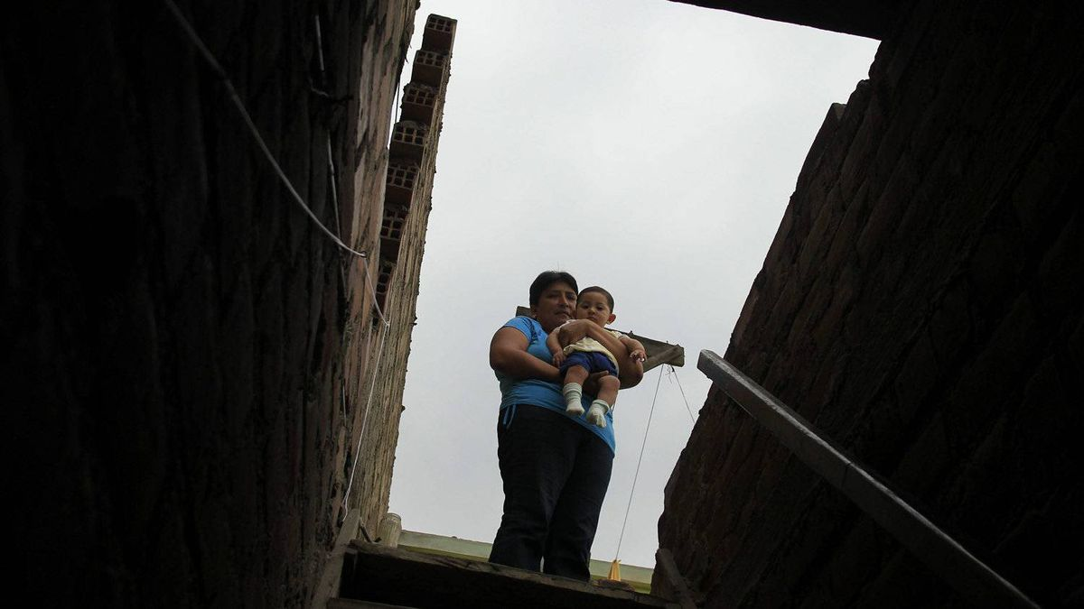 Giovanna Figueroa (wife of injured Peruvian Javier Alba) carries her son Ashraf Alba (6-months-old) at her home in Comas.