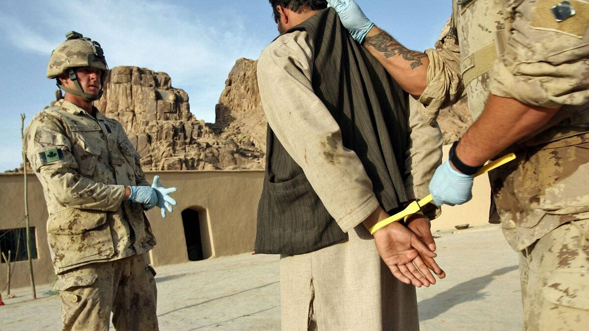 A suspected Taliban prisoner is searched, handcuffed, and processed by Canadian soldiers in northern Kandahar province, Afghanistan, on May 10, 2006.