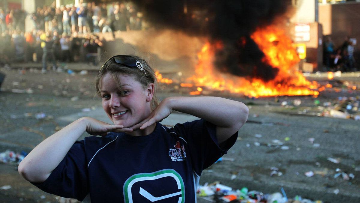 A woman poses for photos in front of an overturned pickup truck as it burns in downtown Vancouver a during rioting after the Canucks lost the Stanley Cup Final to the Boston Bruins.