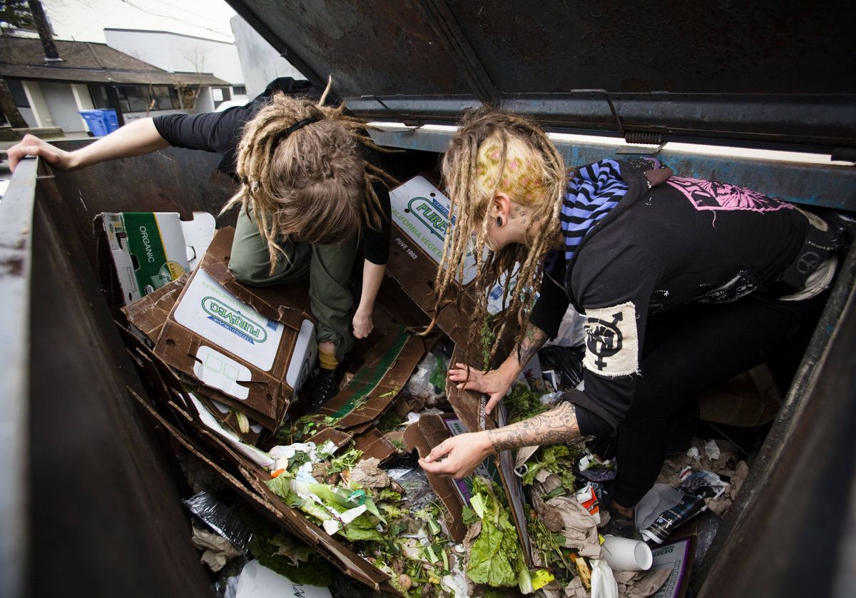 Mya Wollf (R), and Robin Pickell, 23, who are both 'freegans', sort through a dumpster for edible food in an alley behind Commercial Drive.