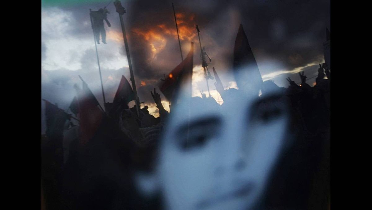 Anti-Gaddafi protesters hanging effigies of Libyan leader Muammar Gaddafi are reflected in a photo of a youth who was killed in the recent clashes in Benghazi March 6, 2011.