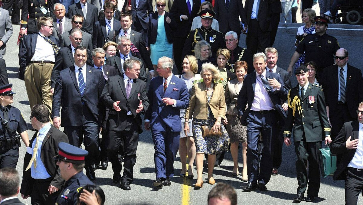 Prince Charles, alongside his wife Camilla, talks with New Brunswick Premier David Alward and Heritage Minister James Moore during a walk about Saint John, N.B., on Monday, May 21, 2012. The royal couple are visiting to Canada to mark the Queen's Diamond Jubilee.