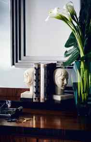 COMBINE AND CONSTRAST As you'll likely note in Baz Luhrmann's upcoming (3D!) Great Gatsby flick, black, white and metallic tones are integral to the art-deco palette. This vignette, built around a pair of vintage ivory bookends atop a polished walnut cabinet, blends all three to dramatic effect.