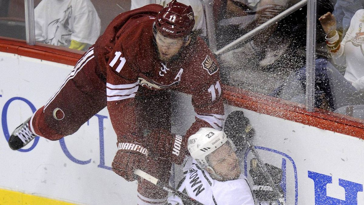 Ice sprays as Phoenix Coyotes' Martin Hanzal (L) crashes into the boards with Los Angeles Kings' Dustin Brown during the third period of Game 2 of the NHL Western Conference hockey finals in Glendale, Arizona, May 15, 2012.