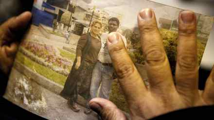 Patricia Aguilar, the widow of Peruvian migrant worker Enrique Leon, touches a photo of her and her long-time partner in Toronto on Tuesday, Feb. 21, 2012.