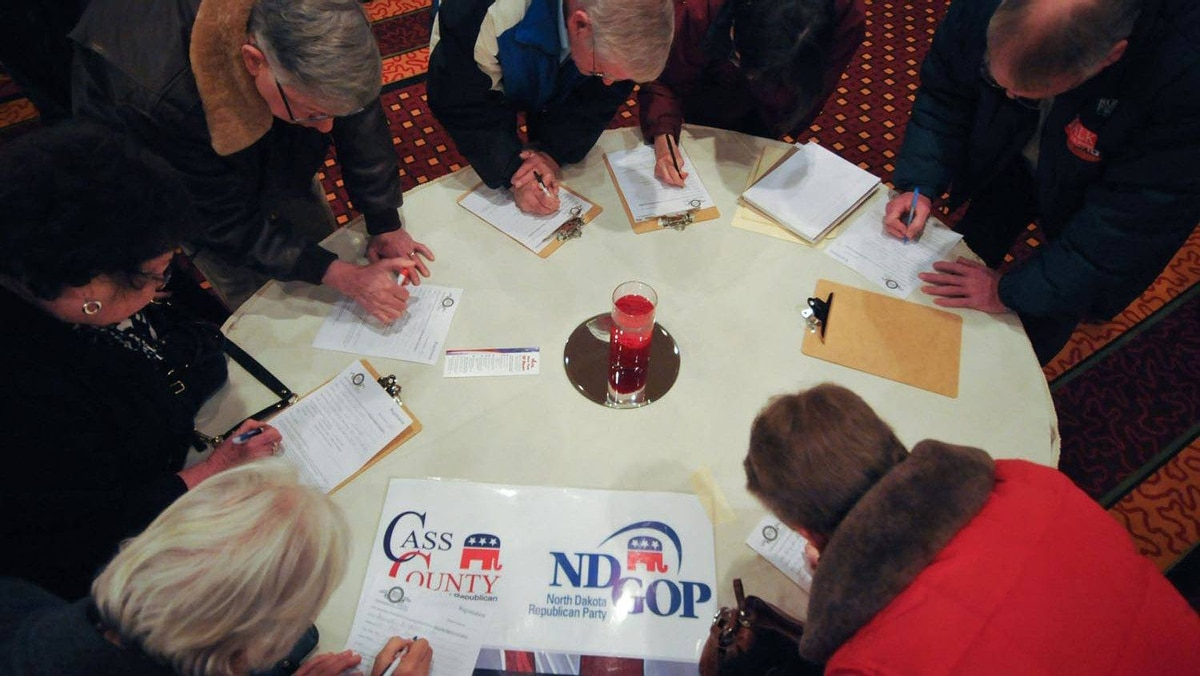 Voters gather around a table as they fill in registration forms at a caucus site in Fargo, N.D., on Super Tuesday, March 6, 2012.