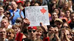 A sign is held above the crowd at a pre-election gathering in London, Ont., Saturday, April 30, 2011.