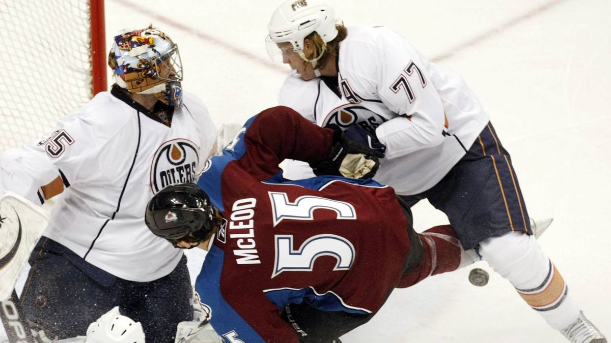 Colorado Avalanche winger Cody McLeod tangles with Edmonton Oilers goalie Nikolai Khabibulin (L) and defenseman Tom Gilbert (R) during their NHL hockey game in Denver April 10, 2011. The Avalanche won 4-3 in OT. REUTERS/Rick Wilking