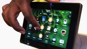 A worker demonstrates the new BlackBerry Playbook in the BlackBerry booth during the 2011 International Consumer Electronics Show at the Las Vegas Convention Center January 6, 2011.