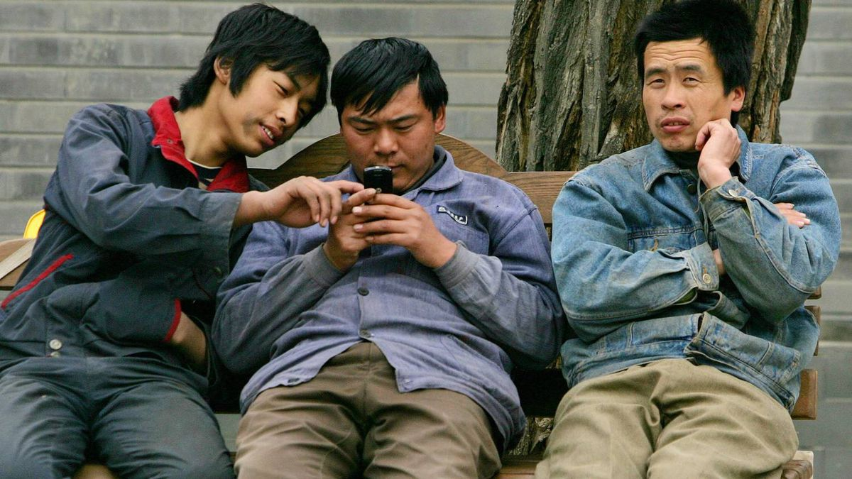 Chinese migrant workers use a cell phone in Beijing