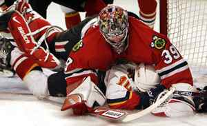 Chicago Blackhawks goalie Nikolai Khabibulin, top, of Russia, tumbles over Calgary Flames' Tony Amonte during the first period of an NHL hockey game Sunday, March 25, 2007, in Chicago.(AP Photo/Nam Y. Huh)