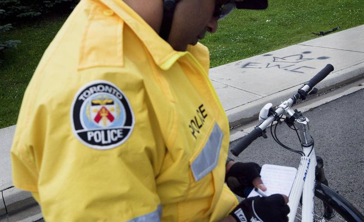 Constable Sheraz Arshad makes note of a new gang tag for the Eglinton West Crips - seen in graffiti on the sidewalk.
