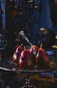 "DON'T BE AFRAID OF THE DARK When styling your spread, amplify the gruesome: Serve caramel pears impaled in the ""neck"" with a fork; have blood-red wine, ruby-red port and bubbling ciders on hand."