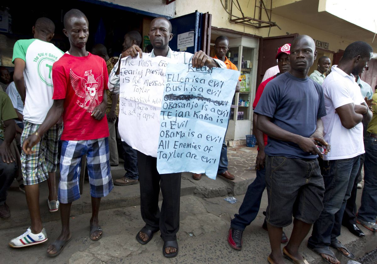 A man holds up signs in support of former Liberian President Charles Taylor holds signs in downtown Monrovia, Liberia as his verdict comes down.