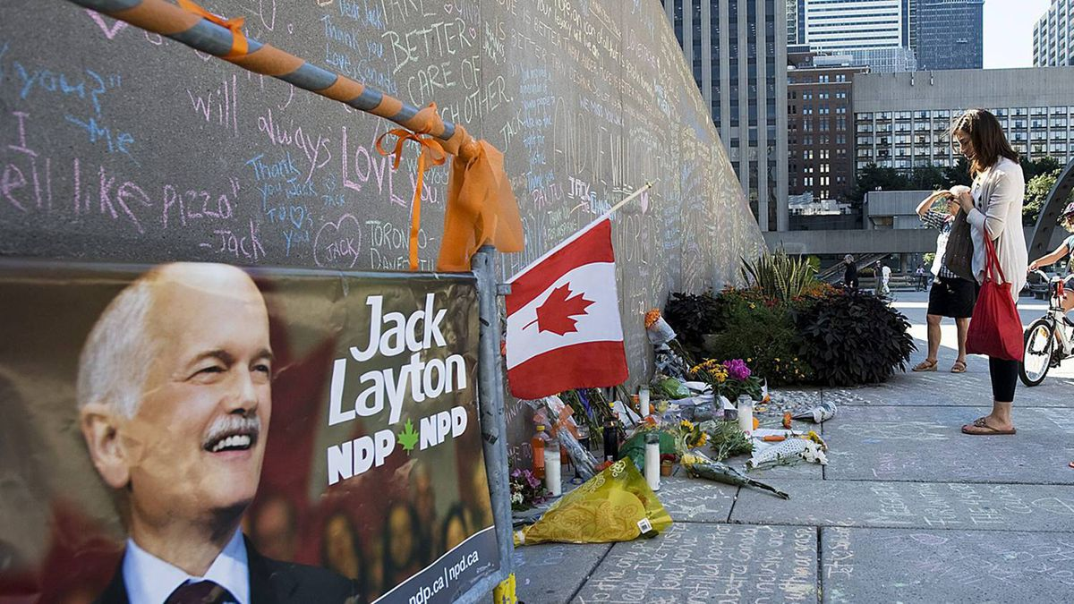 People read from a wall which has been made into a tribute to the late NDP leader Jack Layton at Nathan Phillips Square in Toronto on Tuesday August 23, 2011