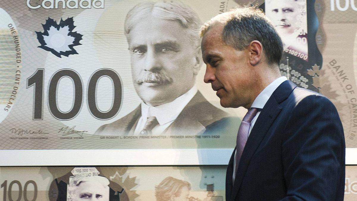 Bank of Canada Governor Mark Carney walks past a poster of the bank's new circulating $100 bill, Canada's first polymer bank note, in Toronto on Nov. 14, 2011.