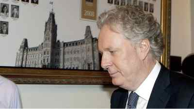 Premier Jean Charest leaves the Quebec National Assembly on Dec. 3, 2010.