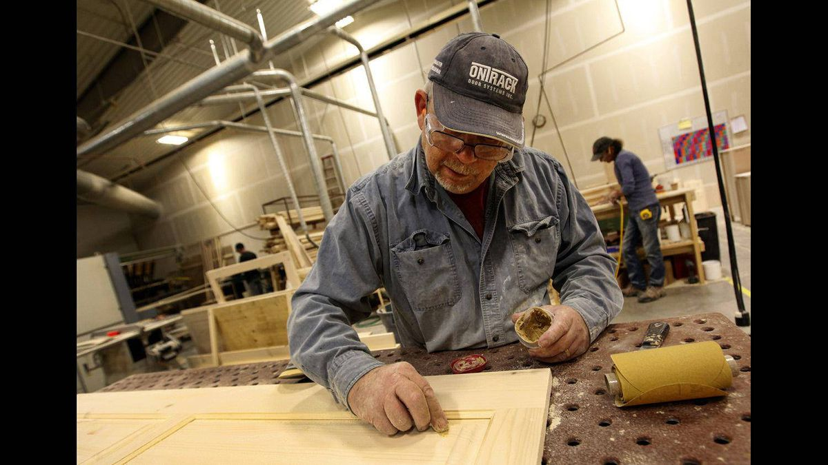 Vokes Furniture employee Bill Bezzo applies wood filler to a panel at the company's factory in Shallow Lake, Ont.