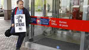 A Canadian Union of Postal Workers member pickets in front of the main post office on Graham Avenue in Winnipeg.
