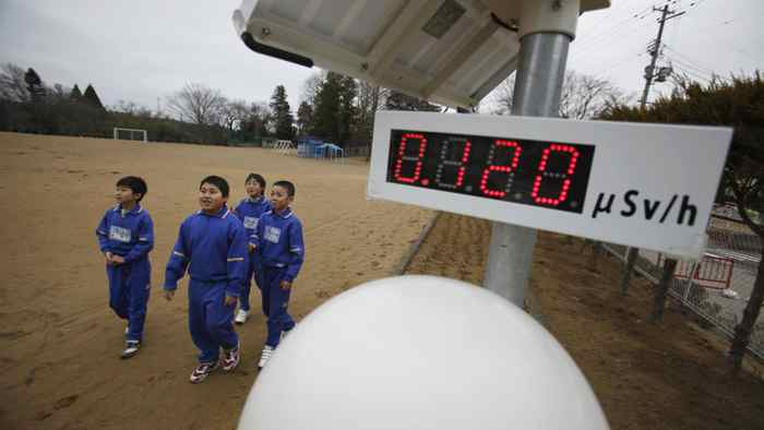 Students walk near a geiger counter at Omika Elementary School, located about 21 km from the tsunami-crippled Fukushima Daiichi nuclear power plant in Japan on March 8, 2012.