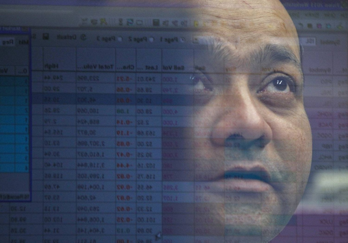 A computer screen displaying stock information is reflected in the window of a booth where a broker is monitoring the markets at Karachi's Stock Exchange March 19, 2012.