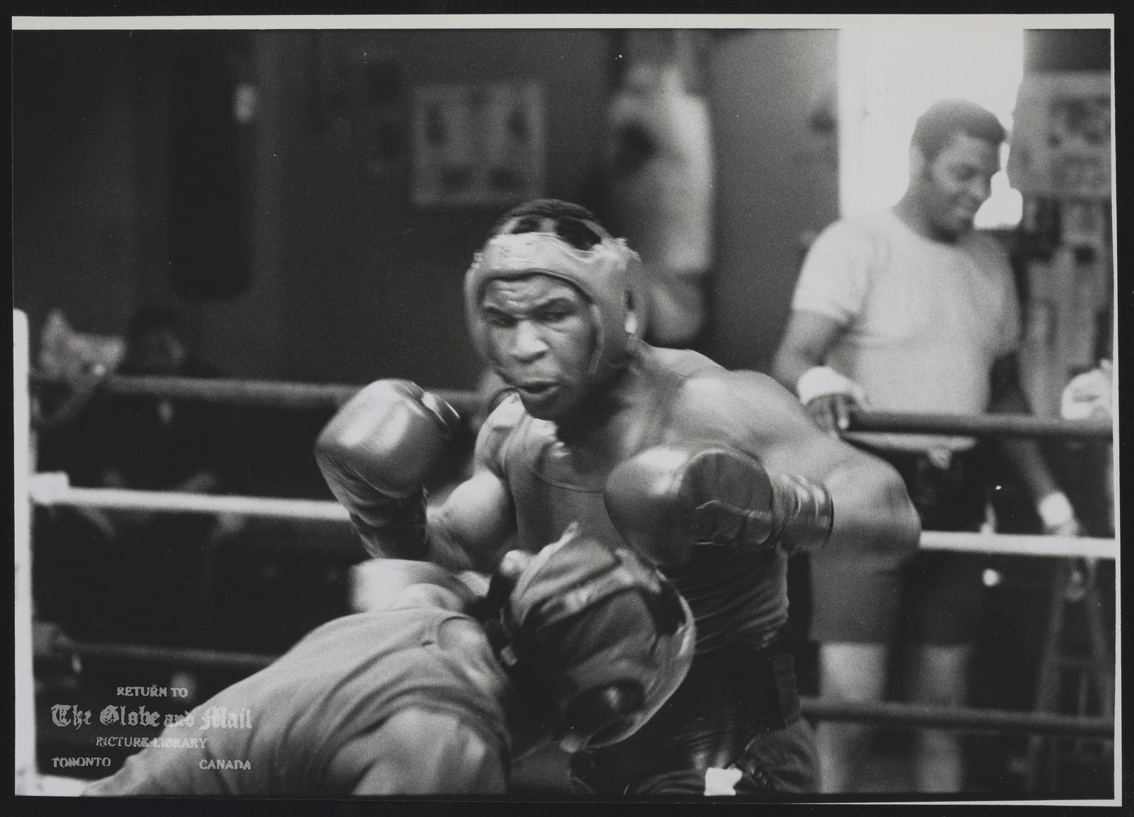 The notes transcribed from the back of this photograph are as follows: MIKE TYSON BOXING MIKE TYSON, THE GREAT BLACK HOPE, SPARS IN A TRAINING CAMP AT CATSKILL, N Y., IN 1986.
