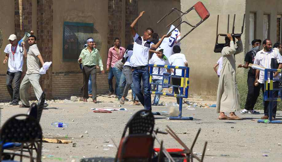 An Egyptian supporter of the former Egyptian president throws a chair as clashes erupted between loyalists and foes of Egypt's former president who is being tried on murder charges.