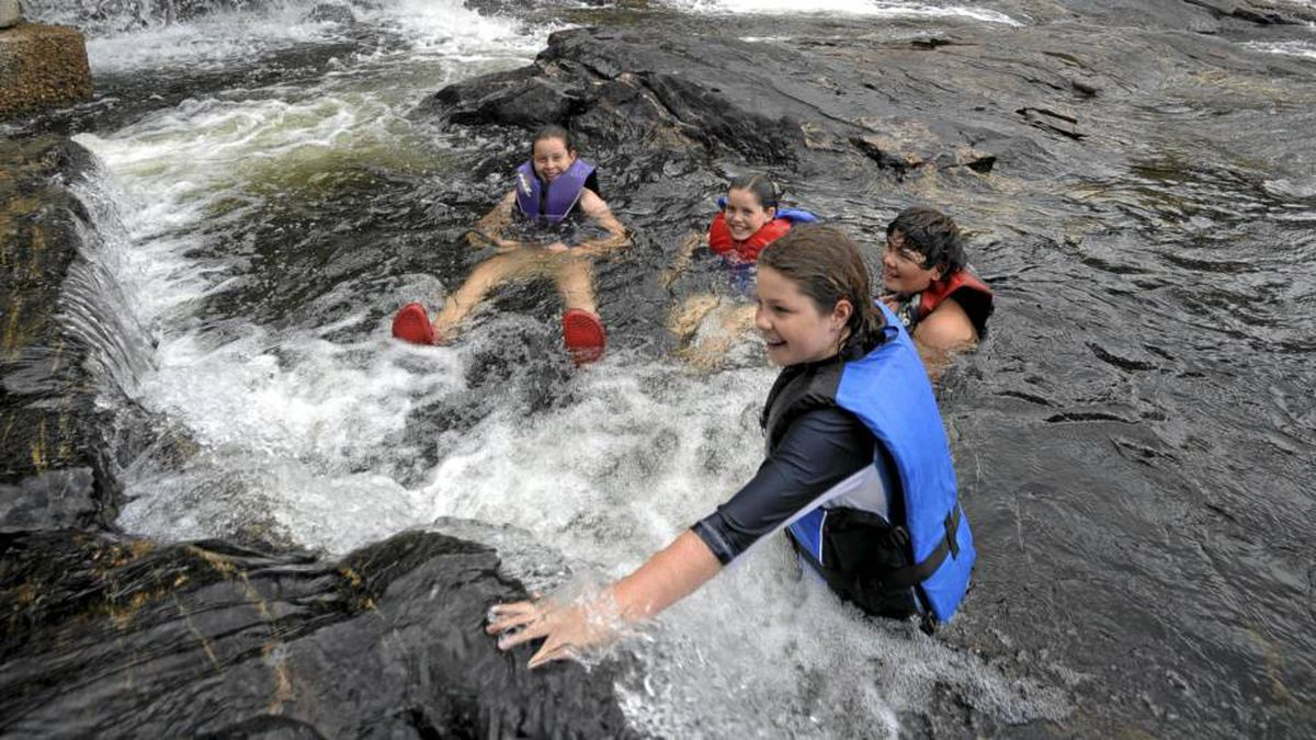 Children play in the waters around Bala Falls, where a proposed run-of-river hydro station has sparked heated opposition from locals.
