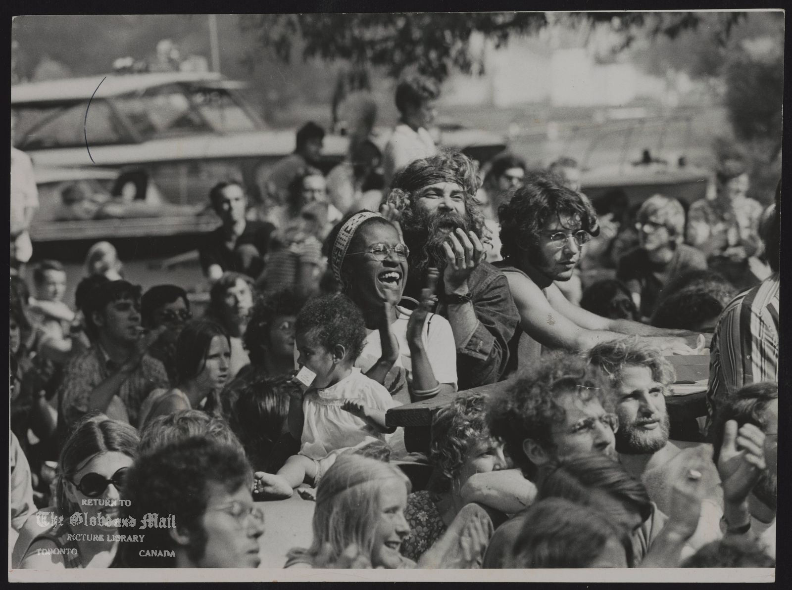 The notes transcribed from the back of this photograph are as follows: MARIPOSA FOLK FESTIVAL (Toronto Island) 80,000 people went to the festival at Centre Island Toronto on the weekend.