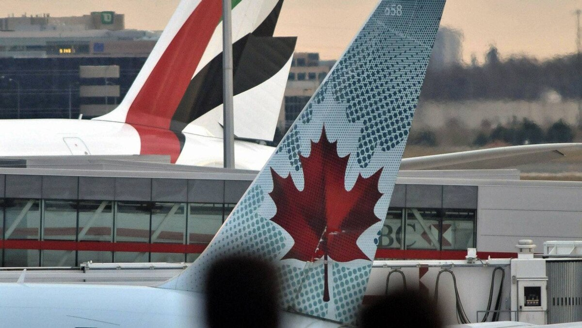 An Emirates Air jet sits at the terminal beside an Air Canada plane at Pearson airport in Toronto on Nov. 19, 2010.