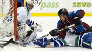 Goalie Roberto Luongo #1 of the Vancouver Canucks watches Brandon Yip #18 of the Colorado Avalanche try and get a shot on net while lying on top of Canucks Andrew Alberts #41 during the second period in NHL action on October 26, 2010 at Rogers Arena in Vancouver, British Columbia, Canada.