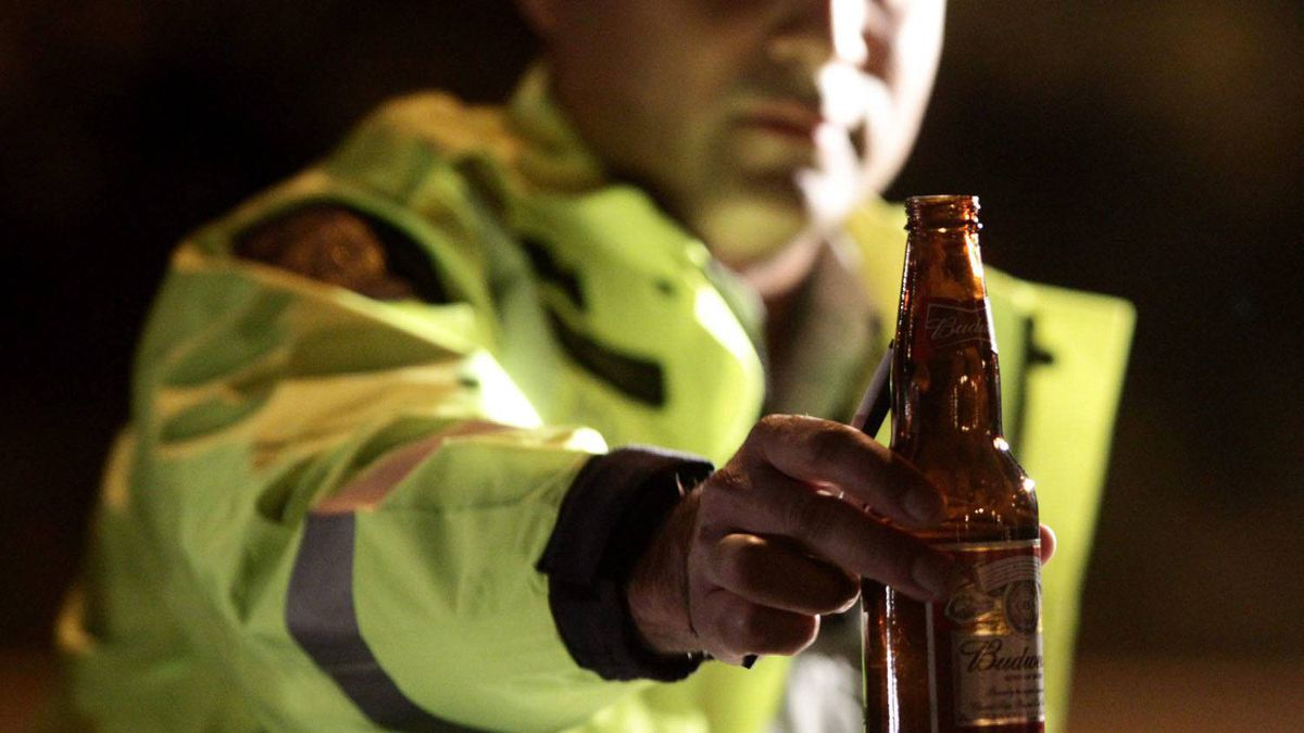 RCMP Cnst. Faz Majid removes an open bottle of beer from a motorist's car during a roadside check in Surrey, B.C., on September 24, 2010.