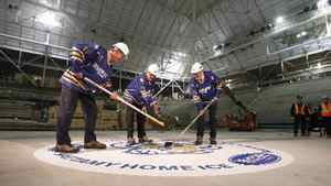 Peter Gilgan, founder and CEO of Mattamy Homes, left, faces off against Sheldon Levy, president and vice-chancellor of Ryerson University during a ceremonial puck drop by John Carmichael, MP for Don Valley West, inside the old Maple Leaf Gardens on Nov. 29, 2011.