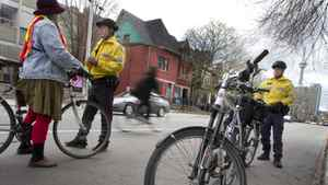 "Toronto Police Constable Blair Begbie, right, and Constable Vince Wong work a detail on Beverly Street south of Baldwin Street in Toronto on April 29, 2011. Both officers are ""bike cops"" and were working during the one day bicycle blitz. At this location they were handing out warnings, primarily to cyclists who rode through the four-way stop at this intersection without stopping. The fine for a cyclist is the same as it would be for a motor vehicle."