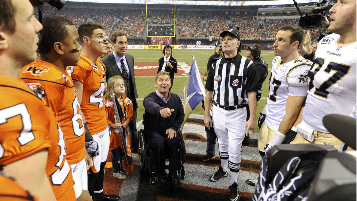 Paralympian Rick Hansen performs the coin toss before the start of the CFL's 99th Grey Cup football game between the Winnipeg Blue Bombers and the B.C. Lions in Vancouver.