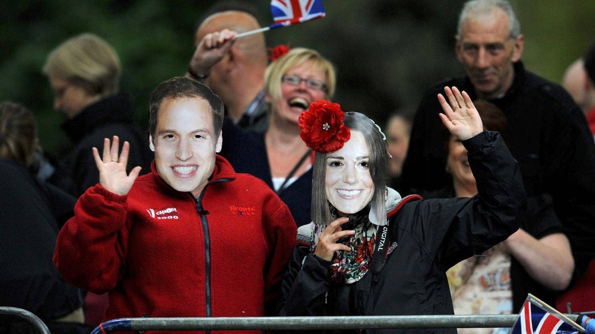 Royal supporters wearing masks of Britain's Prince William and Kate Middleton wave along the processional route in central London.