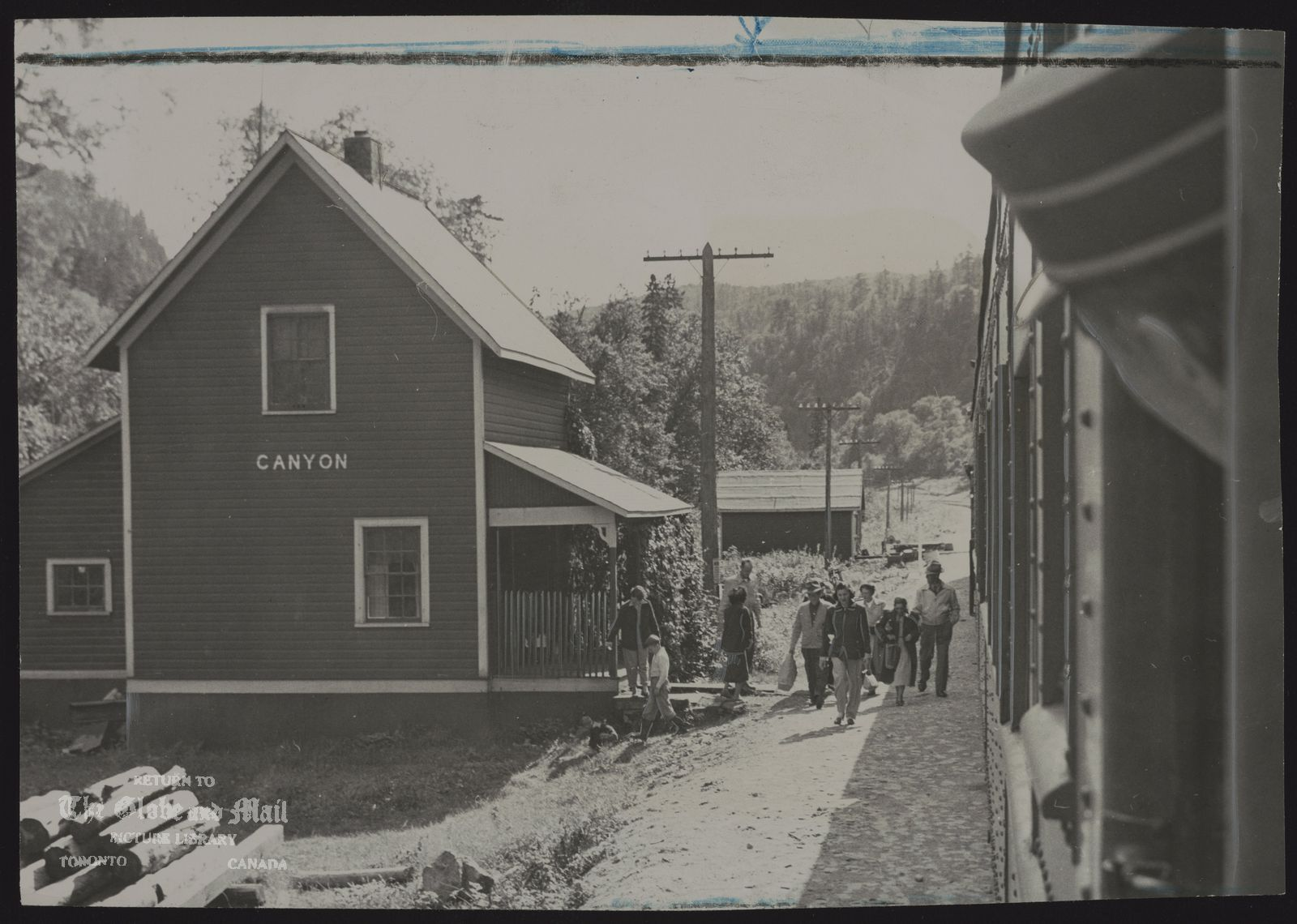 As bundle-carrying passengers walk along the cinder platfrom, Algoma Central train pulls out of Canyon station, heading through rugged grandeur toward Hearst. Station is typical barn-red, clapboard structure, strictly utilitarian.