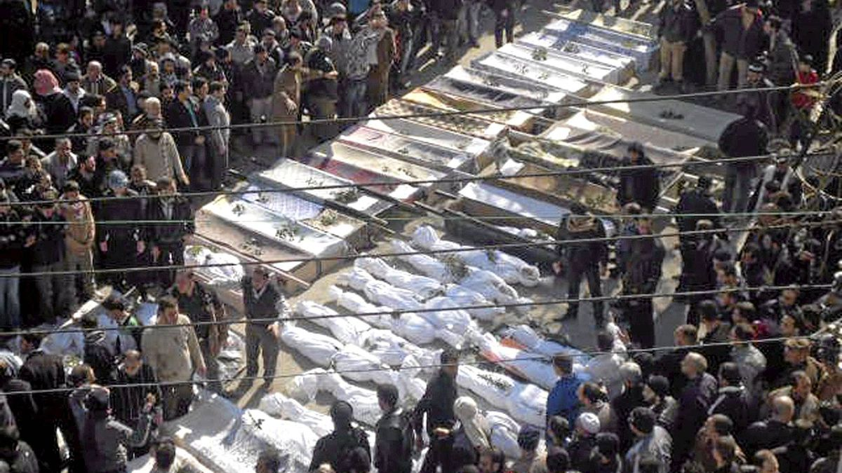 In this citizen journalism image provided by the Local Coordination Committees in Syria, Syrian mourners gather around the coffins of the victims who were killed early Saturday by the bombardment of mortars and rockets during a mass funeral procession, in Khaldiyeh neighborhood in Homs province, central Syria, on Feb. 4, 2012.