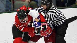 Team Canada's Meghan Agosta, left, wrestles with Team Russia's Yevgenia Dyupina during third period action at the World Women's Ice Hockey Championships Tuesday, April 10, 2012 in Burlington, VT. Canada won the game 14-1.