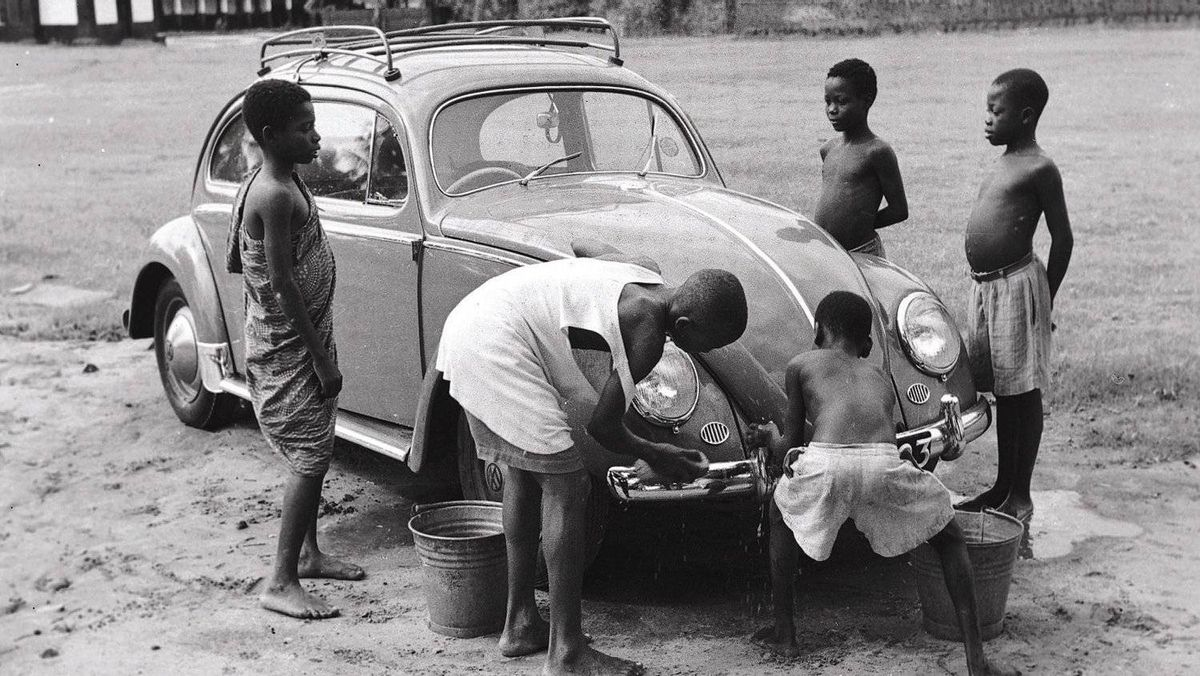 African chlldren wash a 1958 Beetle. The car's simple, rugged design and low cost made it popular worldwide.